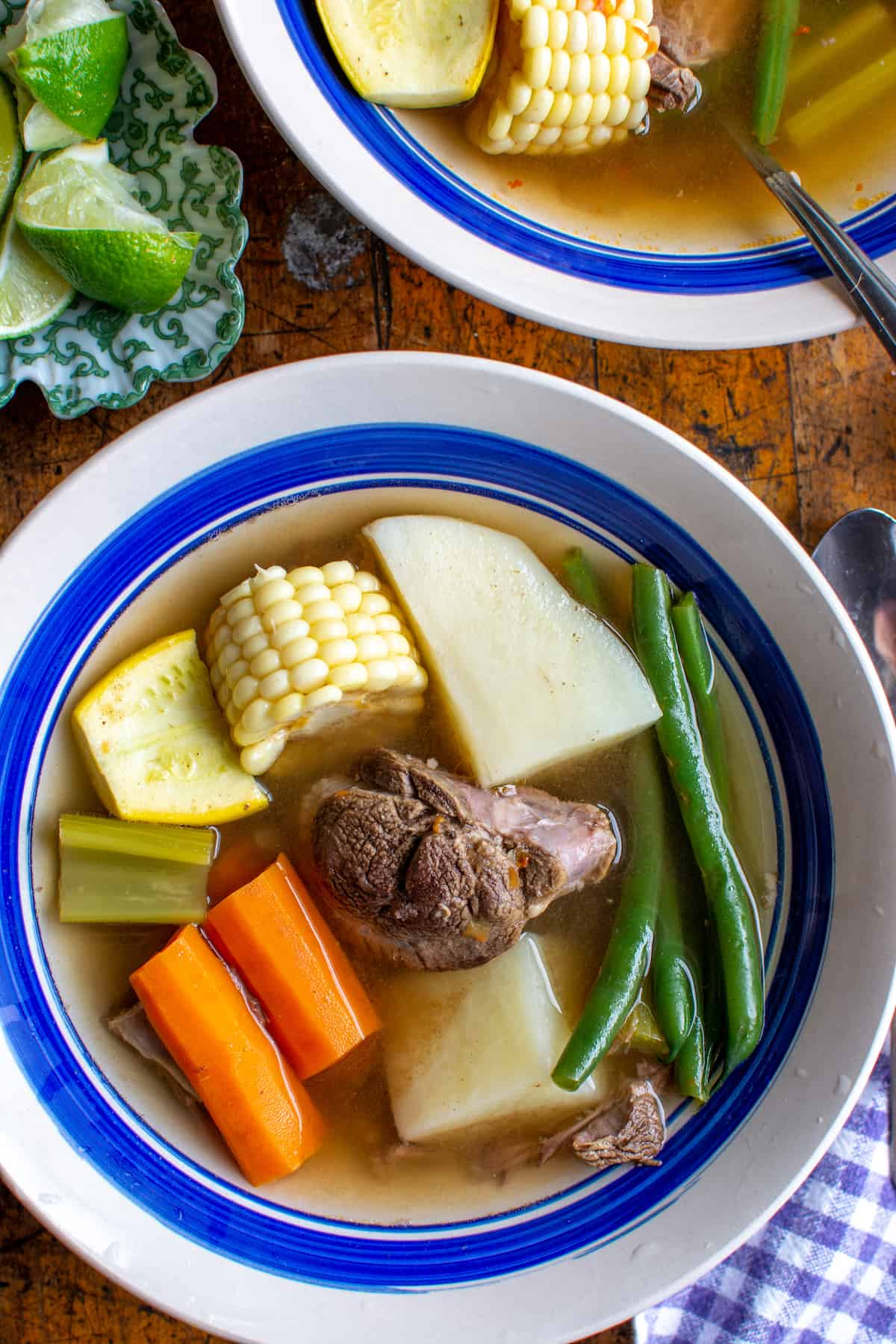 A white bowl with a blue rim filled with Caldo de Res, a Mexican beef and vegetable soup with beef, potatoes, carrots, and green beans.