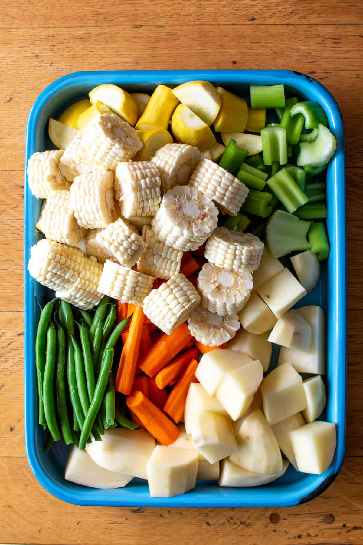 A blue pan filled with vegetables for the Caldo de Res, potatoes, carrots, green beans, corn, celery, and yellow squash all cut into chunks.
