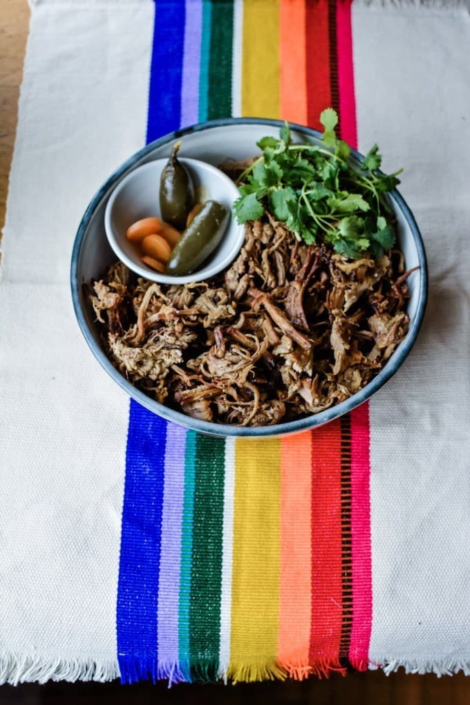 A rainbow tablecloth with a bowl of carnitas on top of it. A small bowl of pickled jalapenos and carrots are next to the carnitas.