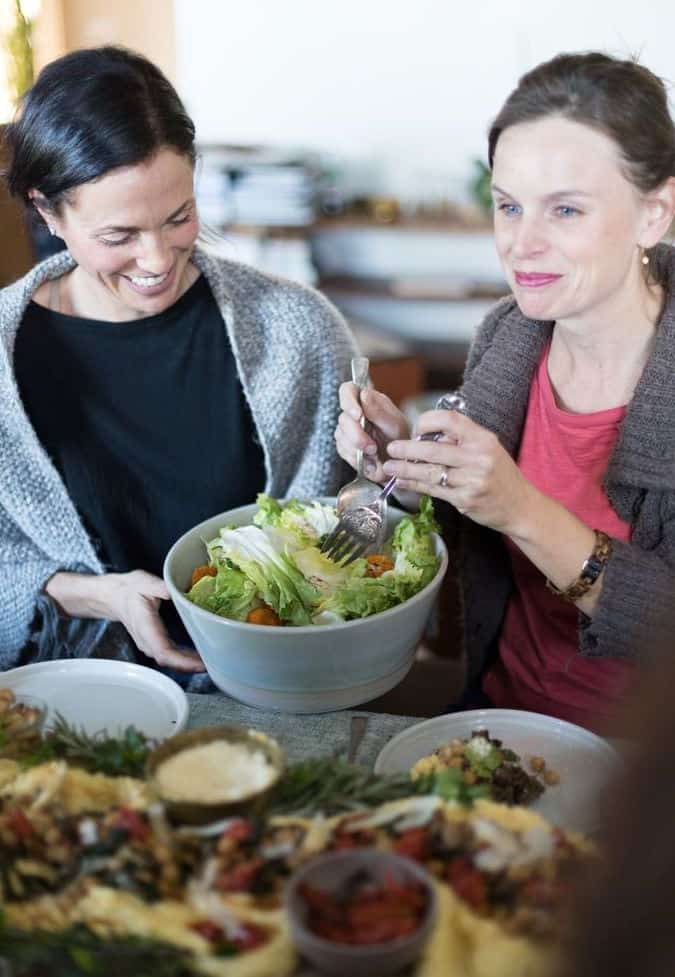 Two women sitting at a table. One is holding a bowl of salad and the other one is serving it.