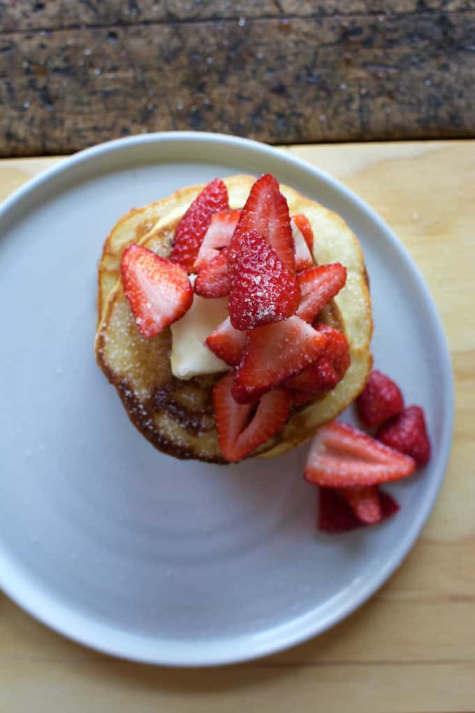 masa harina pancakes with vanilla sugar strawberries sitting on a white plate on a wood table.