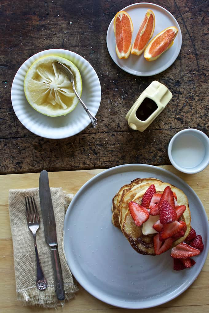 masa harina pancakes with vanilla sugar strawberries on a white plate sitting on a table next to a bowl of grapefruit and a glass of milk.