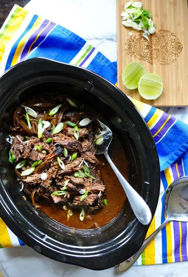 A black ceramic crock filled with shredded meat, sliced scallions, and sauce with a fork stuck in the meat.