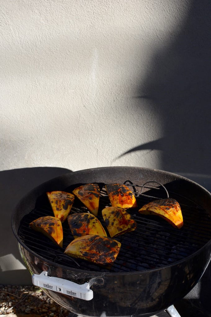 Grilled pumpkin steaks are an excellent way to eat up that delicious Halloween Jack-O-Lantern with creamy black beans and spicy jalapeño pesto sauce!
