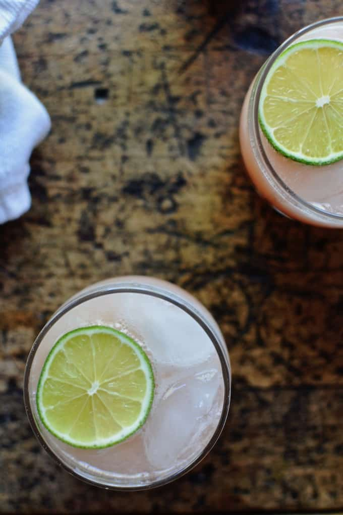 This pale pink Rhubarb Lemonade is perfect for summer and requires no lemon squeezing. The lemons get blended, rind and all, for a sweet and tart drink to beat the heat. #lemonade #pinklemonade #homemadelemonade