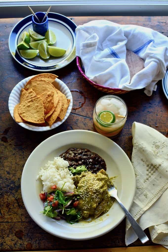 A white plate full of food on a wooden table next to a drink in a glass and a bowl of tostadas.