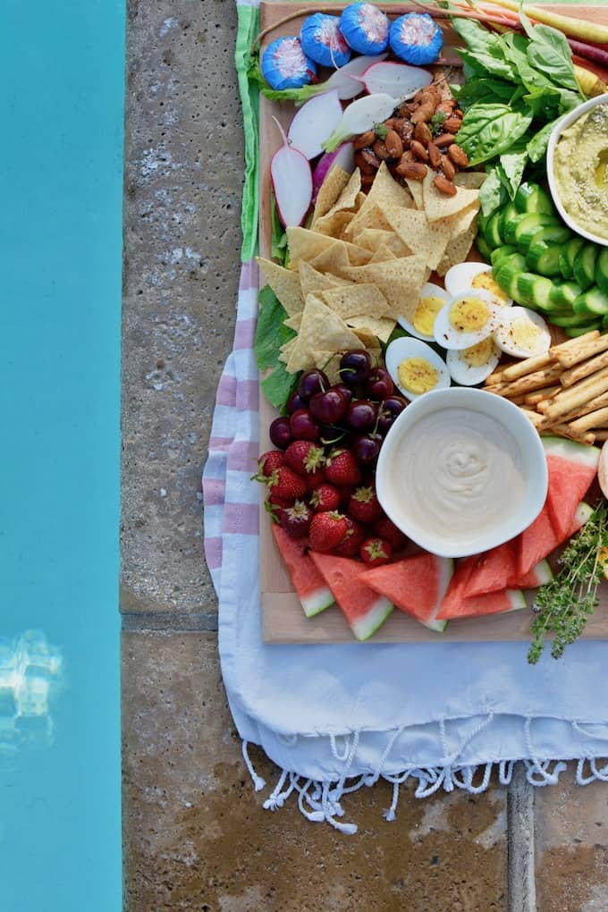 A snack board with fresh fruits and vegetables, bowls of dips, cheese, and snacks.