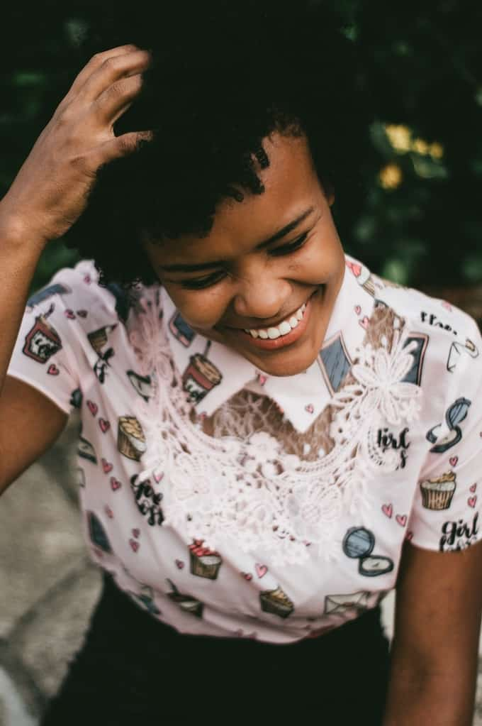 A woman laughing with her hand in her hair. She's wearing a pink shirt with lace around the neck and pictures of cupcakes on it.