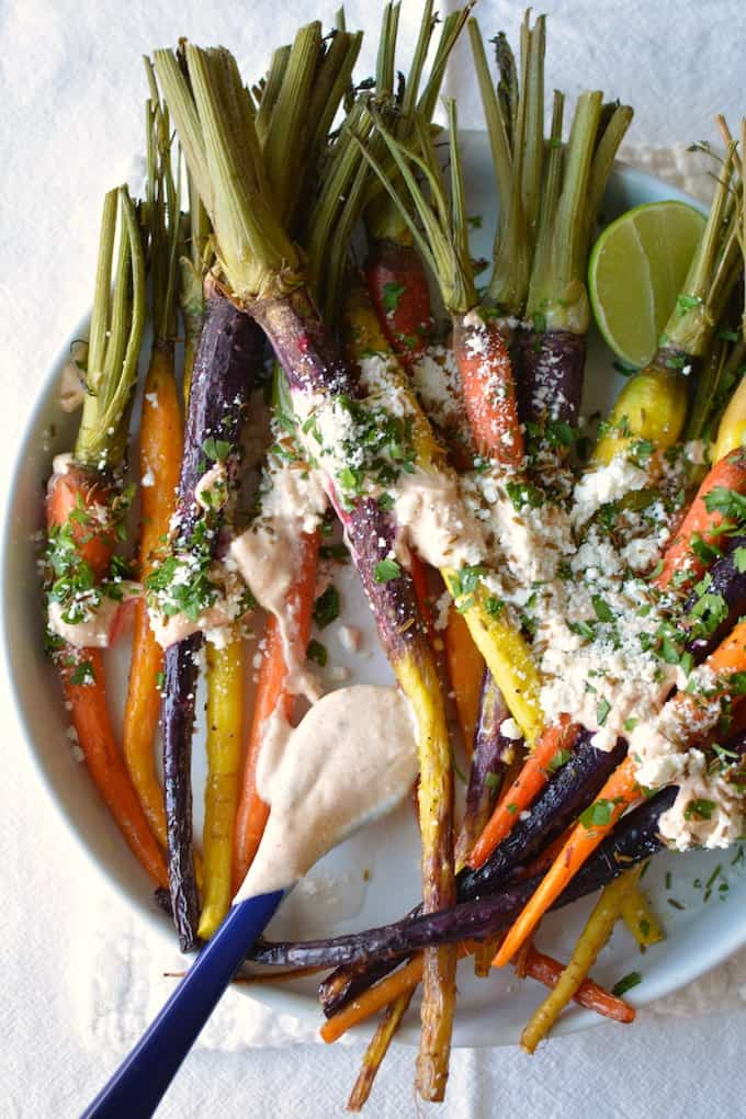 These Roasted Mexican Street Carrots are just like everyone's favorite street corn with cotija cheese, cilantro, and a creamy roasted garlic-lime dressing. Make for a quick and easy holiday side. Goes great with turkey, beef tenderloin, or ham. #roastcarrots #vegetarian #holidayside #easyside #carrots #Mexican #thanksgiving #roastedcarrots