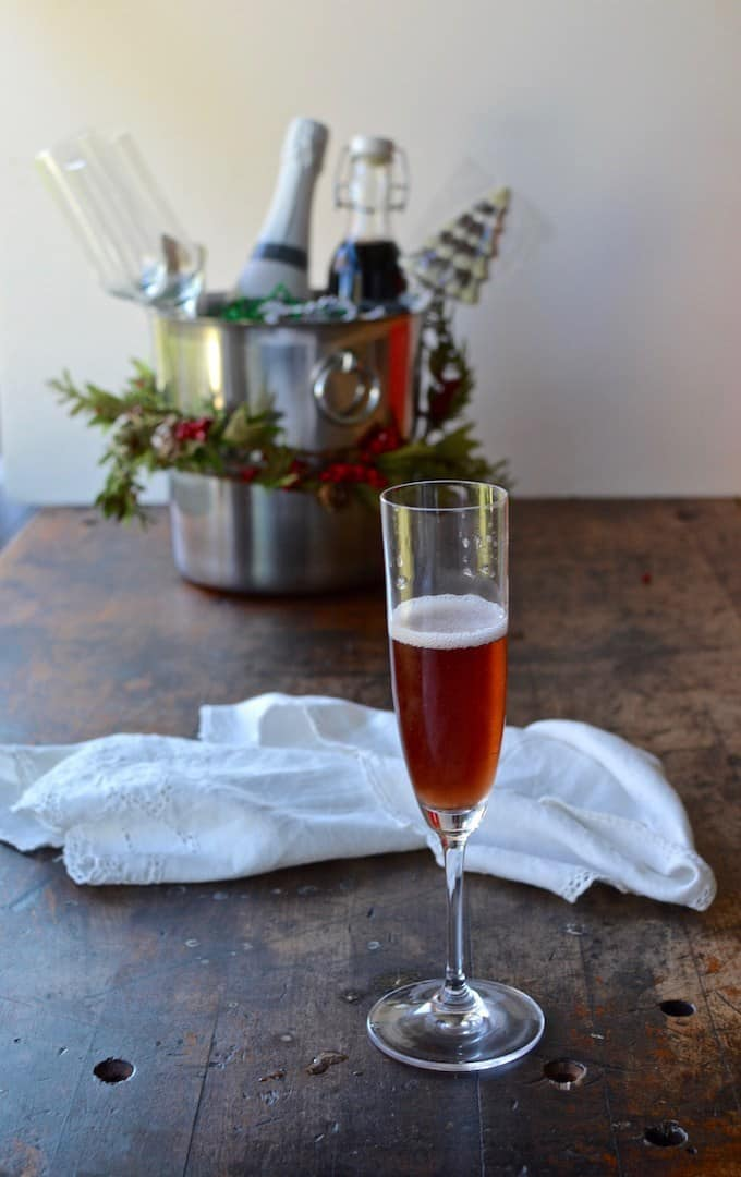 A champagne flute sitting on a wooden table with red liquid in it and foam at the top. A white cloth napkin is sitting behind it.