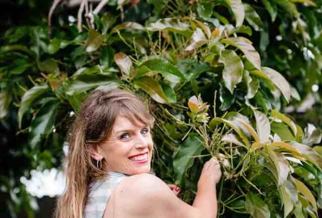 Woman looking over her shoulder standing in front of a avocado tree.