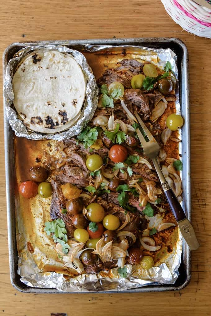 A large pan with flank steak, tomatoes, and shallots, served with tortillas. #holajalapeno