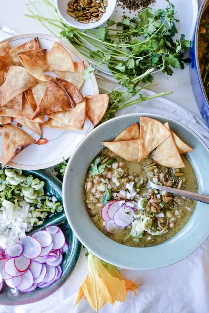A blue bowl filled with pozole soup topped with radish slices and tortilla chips on a white tablecloth.