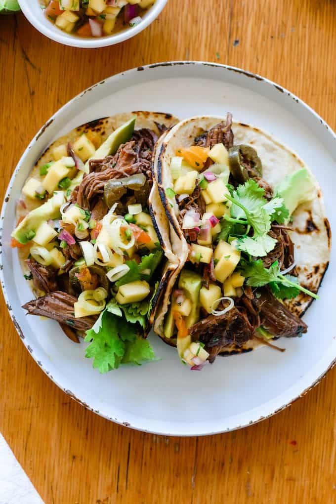 Slow Cooker Beef Tacos on a white plate with mango salsa sitting on top.