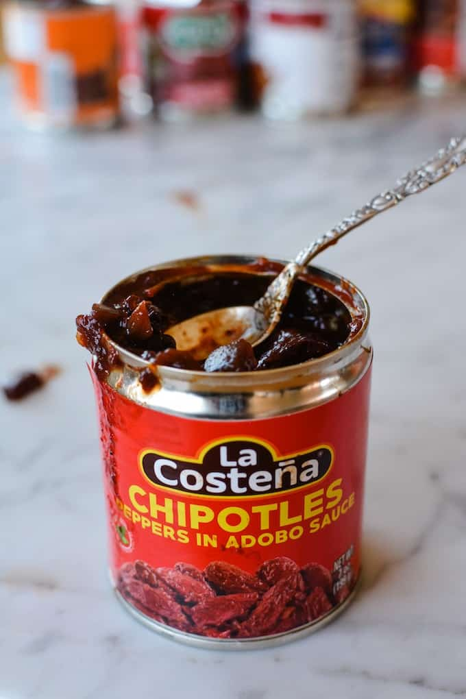 A can of La Costeña chipotles peppers in adobo sauce that has been opened and has a spoon sticking out of the can.