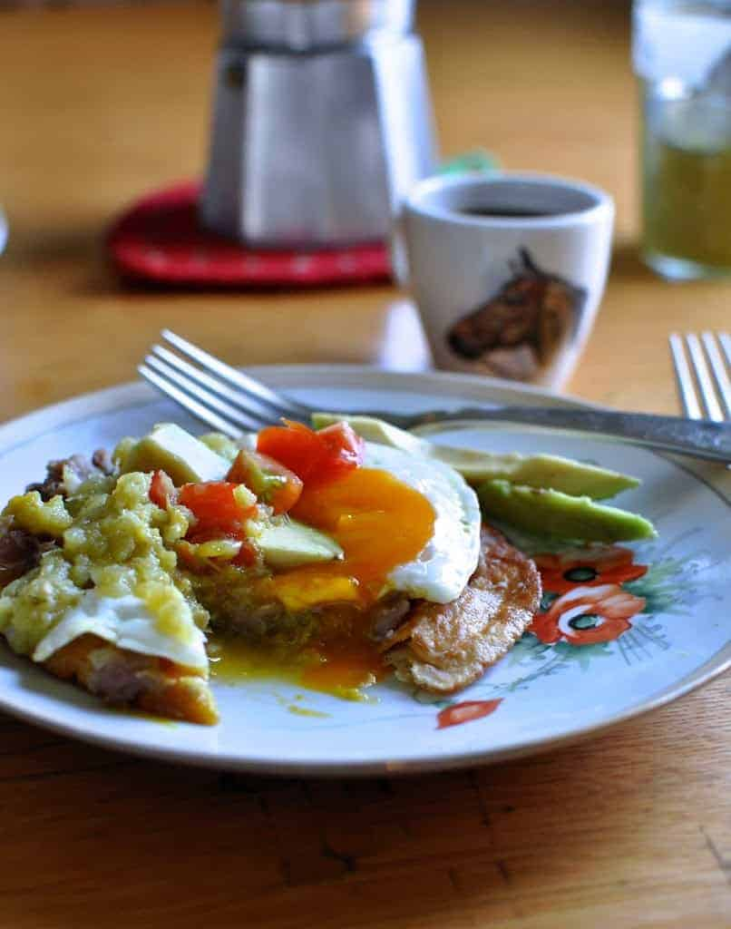 A plate of Huevos Rancheros with an egg on top and a fork on the plate. An espresso cup of coffee sits in the background.