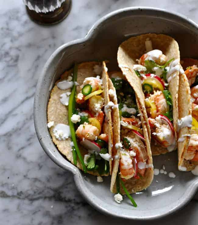 A plate of shrimp tacos sitting on a marble table topped with sliced jalapeños, Mexican Crema, cilantro, and crumbled cheese.
