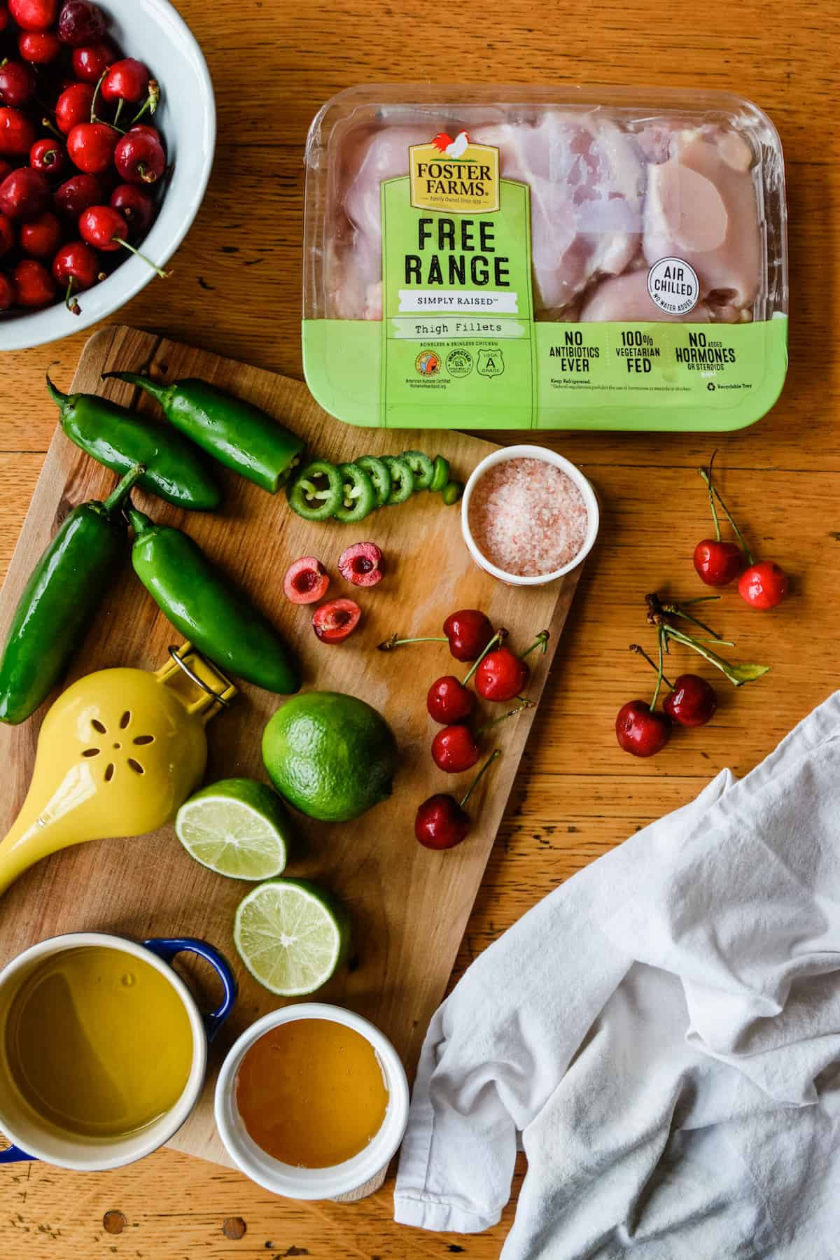 Ingredients to make jalapeno chicken. A bowl of cherries sitting on a wooden table next to a package of chicken and a cutting board.