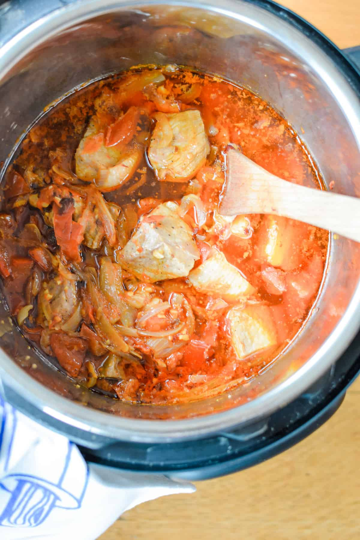 An overhead view of a Instant Pot pressure cooker filled with pieces of pork, onions, and garlic in a tomato sauce. A wood spoon is in the pot.