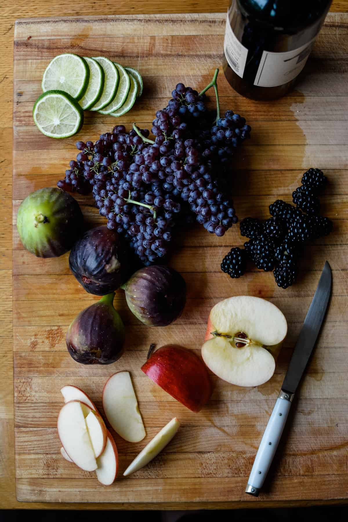 Sliced apples, figs, blackberries, miniature red grapes, lime slices, and a bottle of wine sitting on a wood cutting board.
