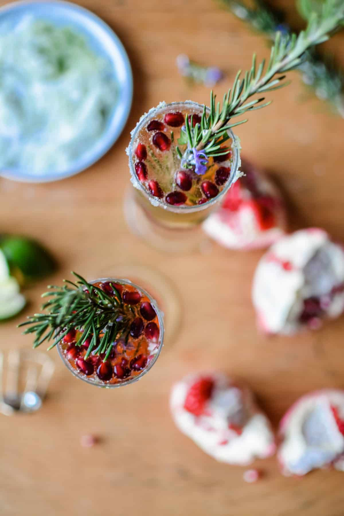 An overhead image of two California Kir Royale Sparkling Wine Cocktails in champagne flutes with pomegranate arils and rosemary sprigs.