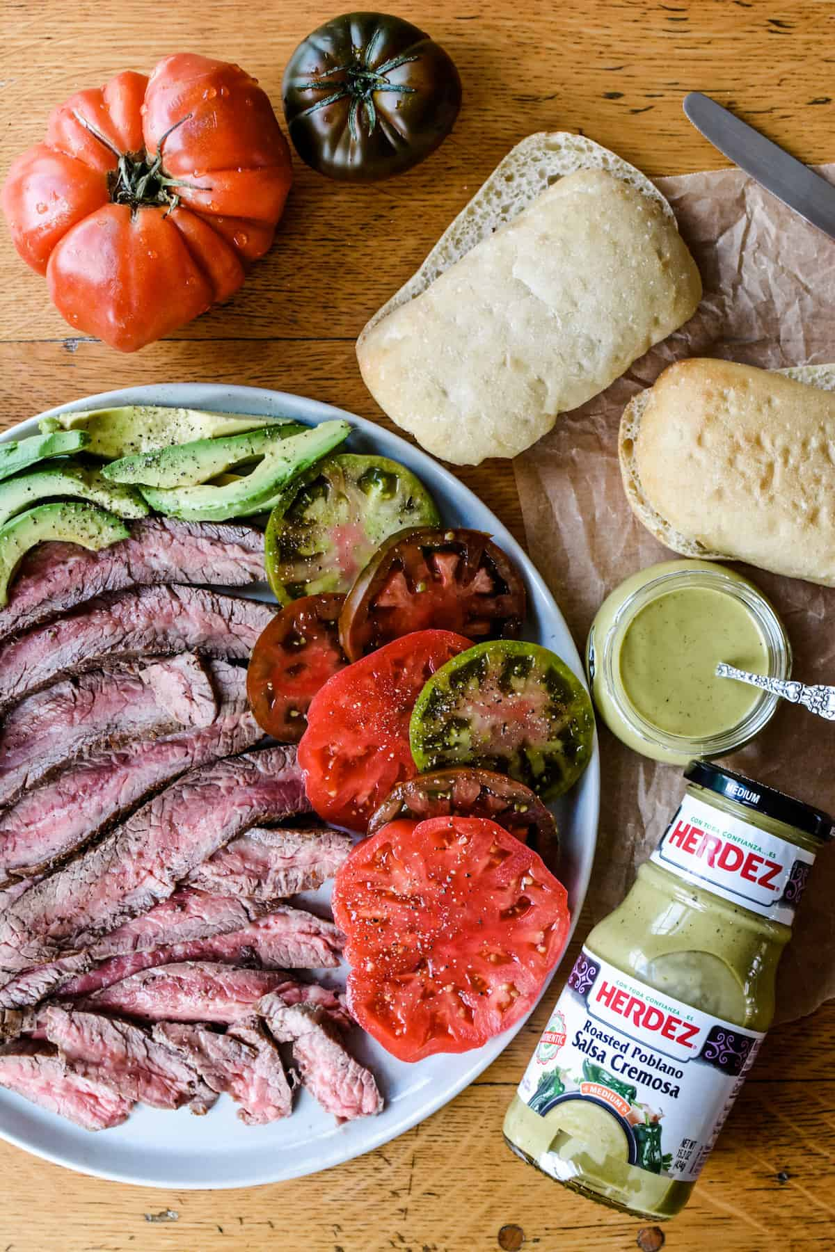 A plate of sliced steak, avocado and tomato slices sitting on a wooden table. Heirloom tomatoes sitting on the side along with rolls cut in half.