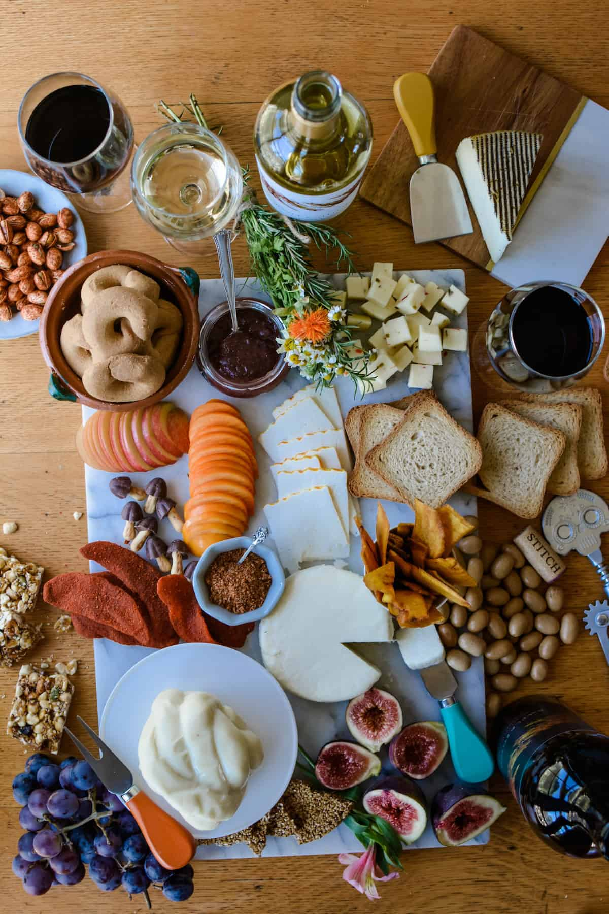 An overhead shot of several cheeses, toasts, figs cut in half, spiced dried mangos, cookies, jam, a bundle of flowers, and glasses of wine.