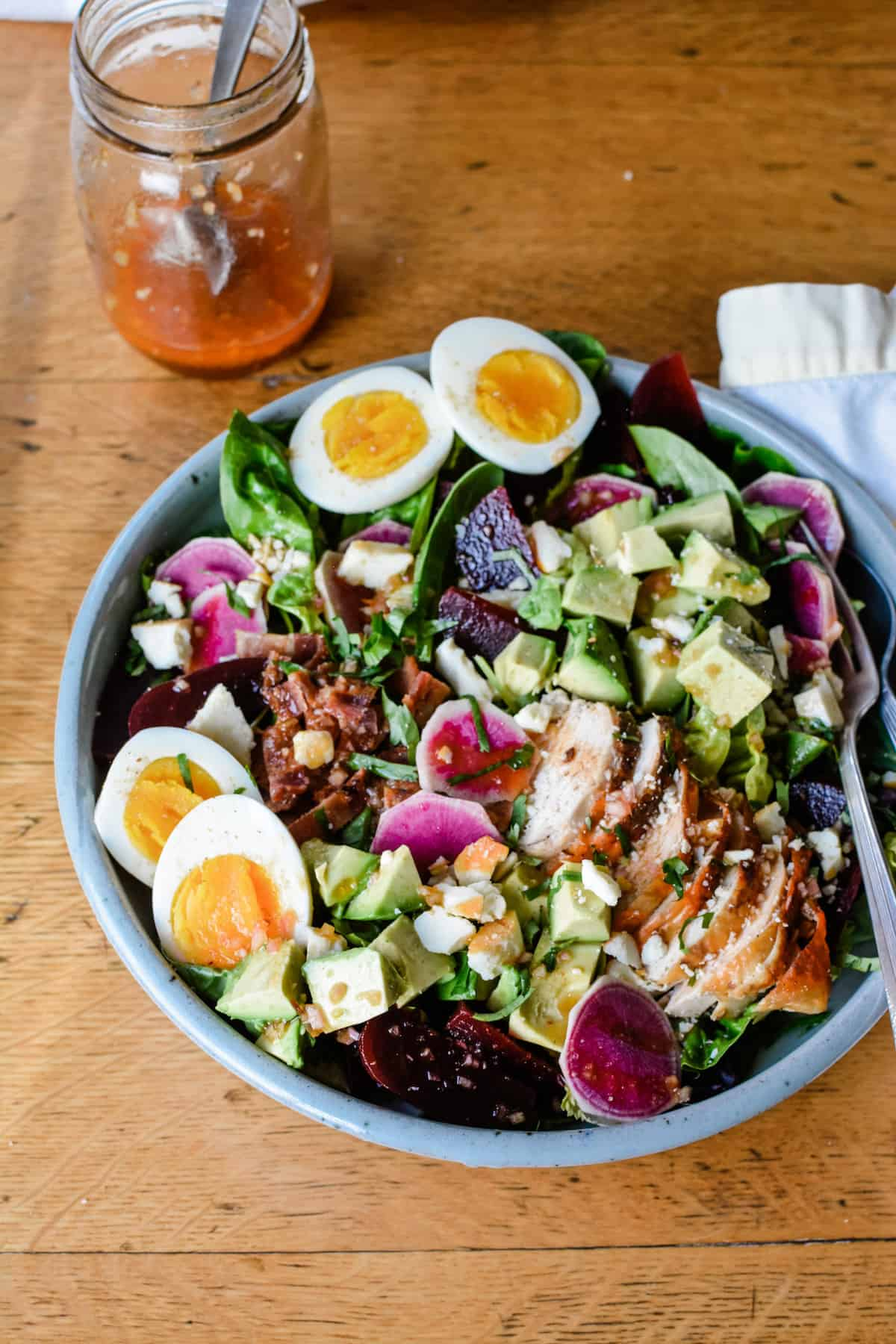 An overhead image of a large salad sitting on a wooden table with a fork in it and a jar of homemade dressing near by.