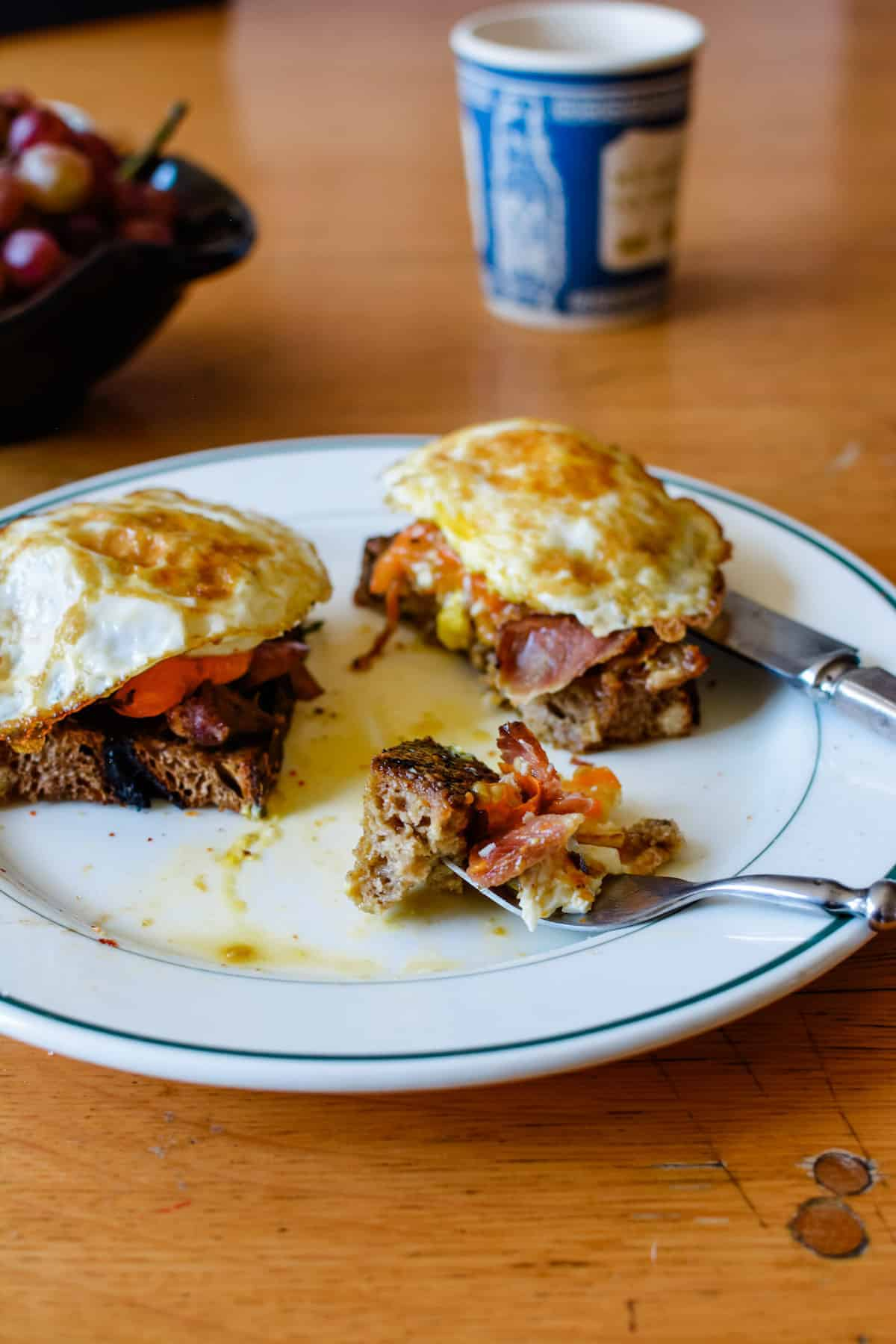 An image of a leftover ham recipe using it to make bruschetta with the ham on toast and a fried egg on top. The bruschetta is cut in two.