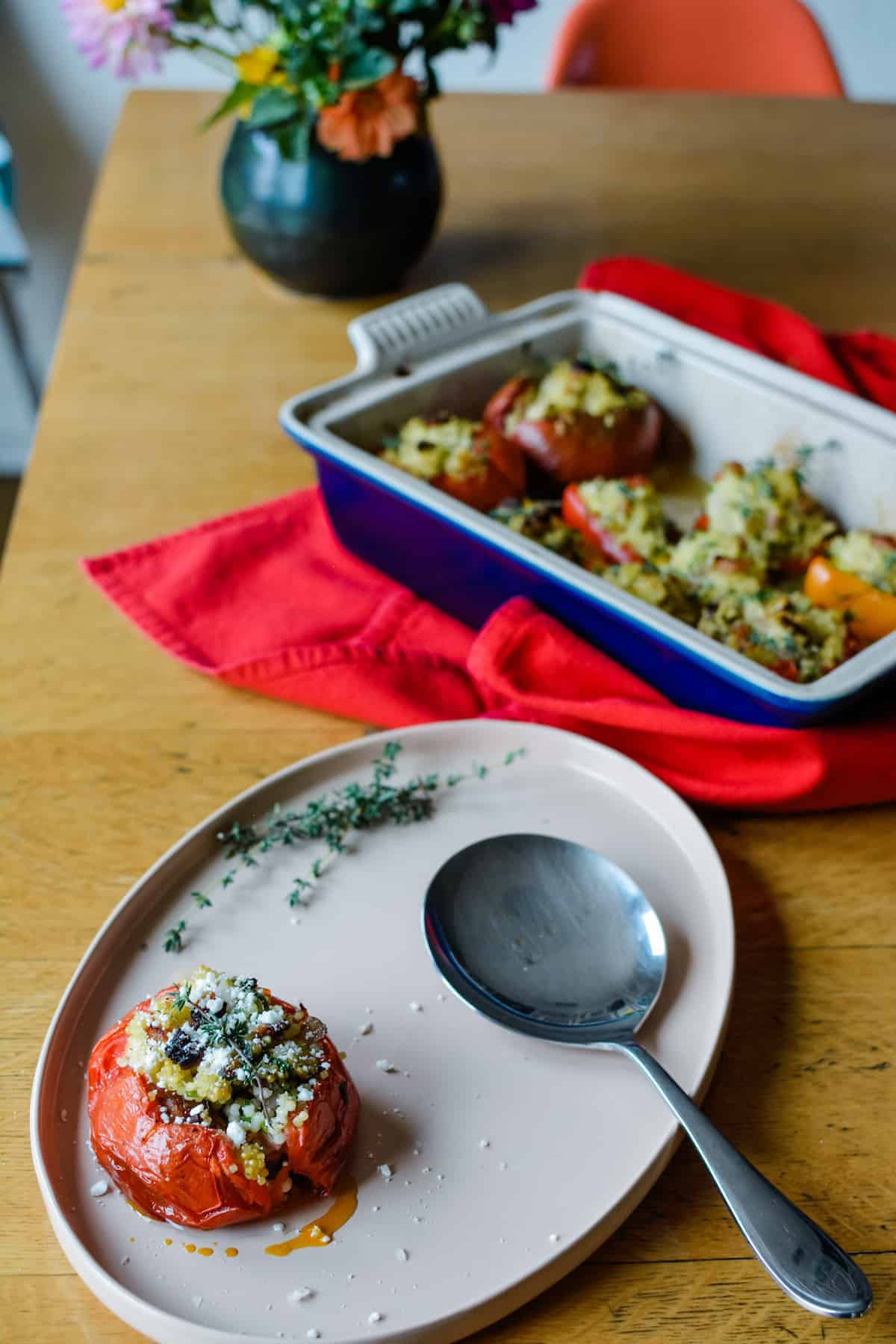 A pink, oval platter with a stuffed tomato on it as well as a stainless steel serving spoon and some thyme leaves.