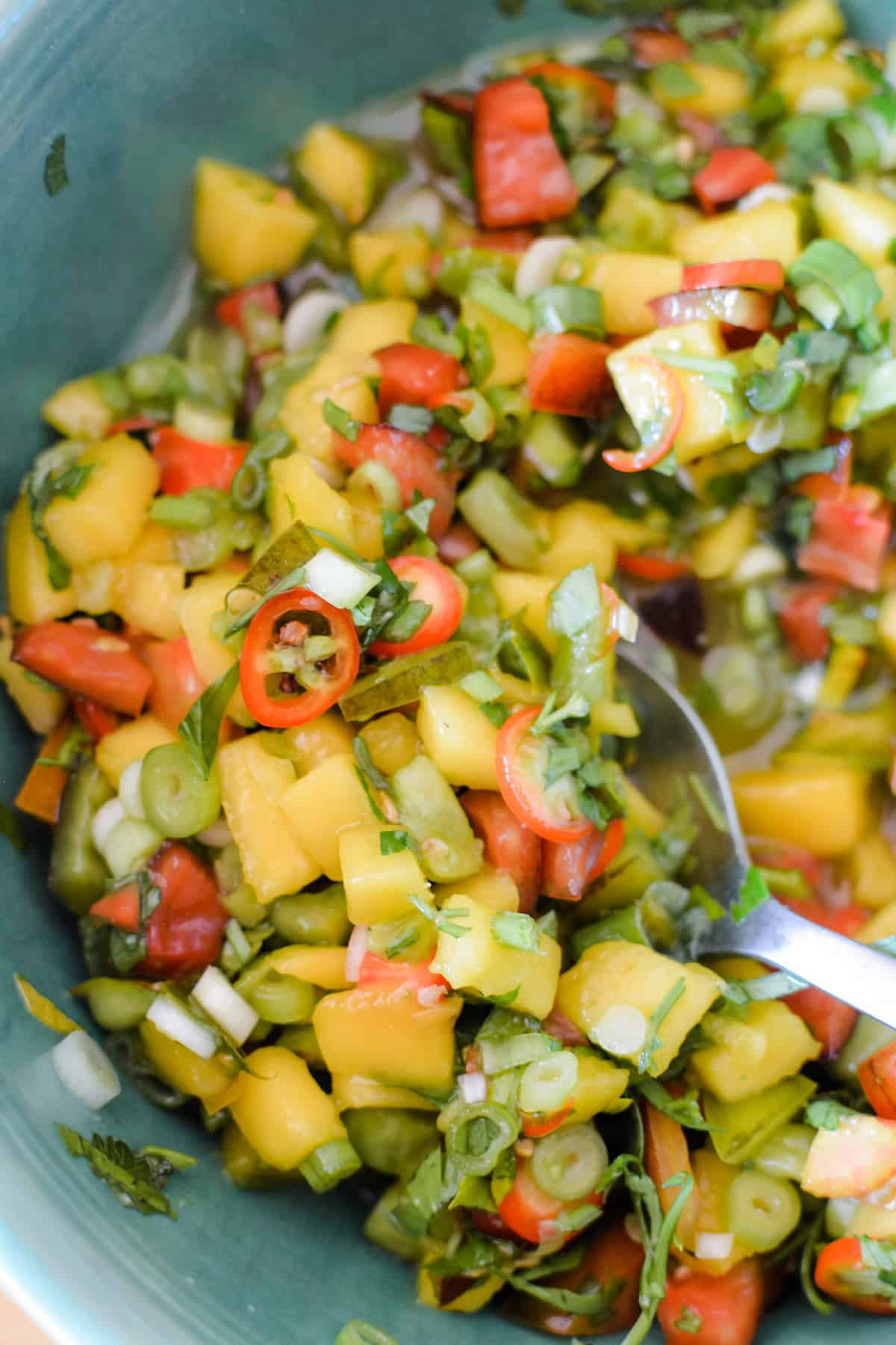 A close up of mango margarita salsa in a bowl with a spoon sticking in the salsa.