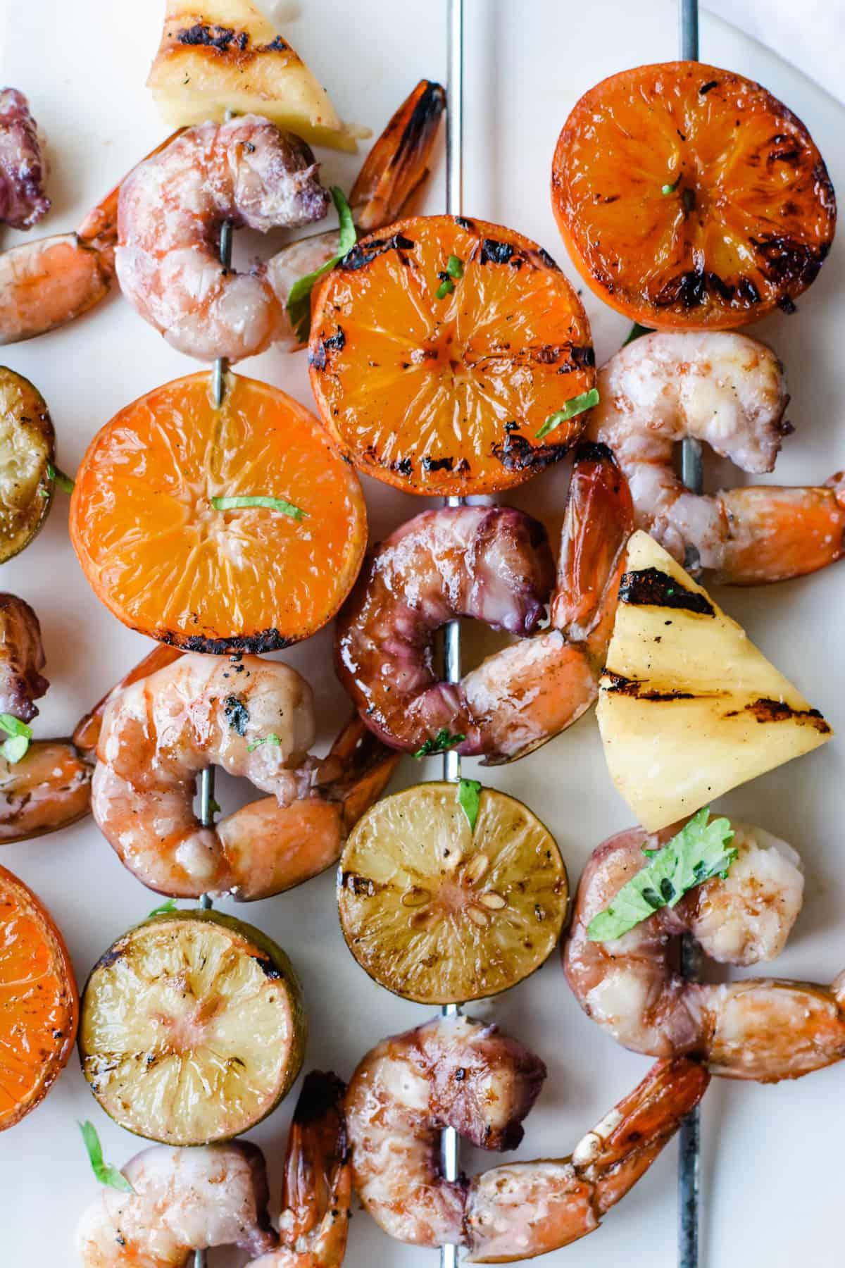 An overhead image of grilled shrimp, grilled tangerine halves, pineapple, and grilled key limes skewered on metal skewers.