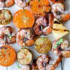 An overhead image of grilled shrimp skewers with charred tangerine halves, pineapple, and halved key limes.