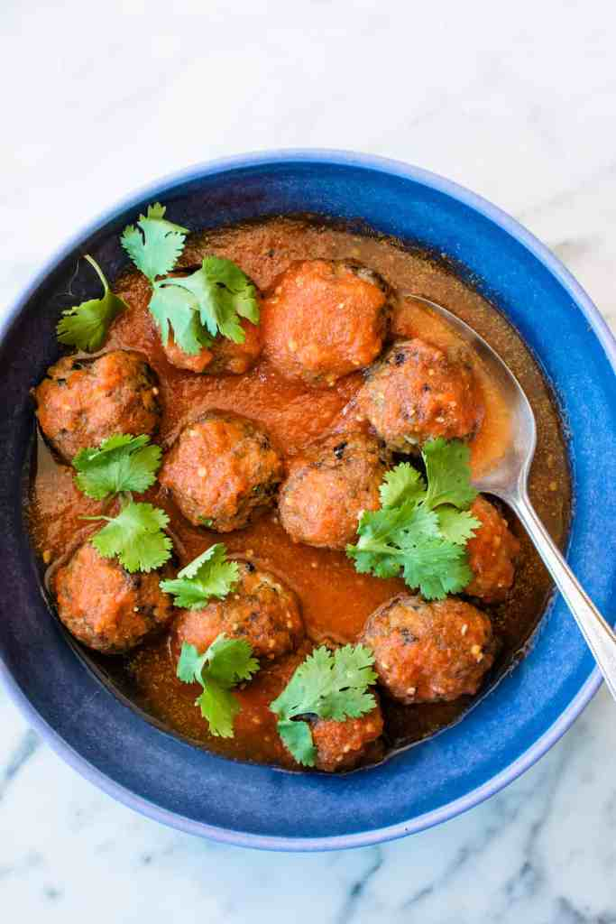 Overhead image of a blue bowl with pork meatballs in tomato sauce and fresh cilantro on top with a spoon in the bowl.