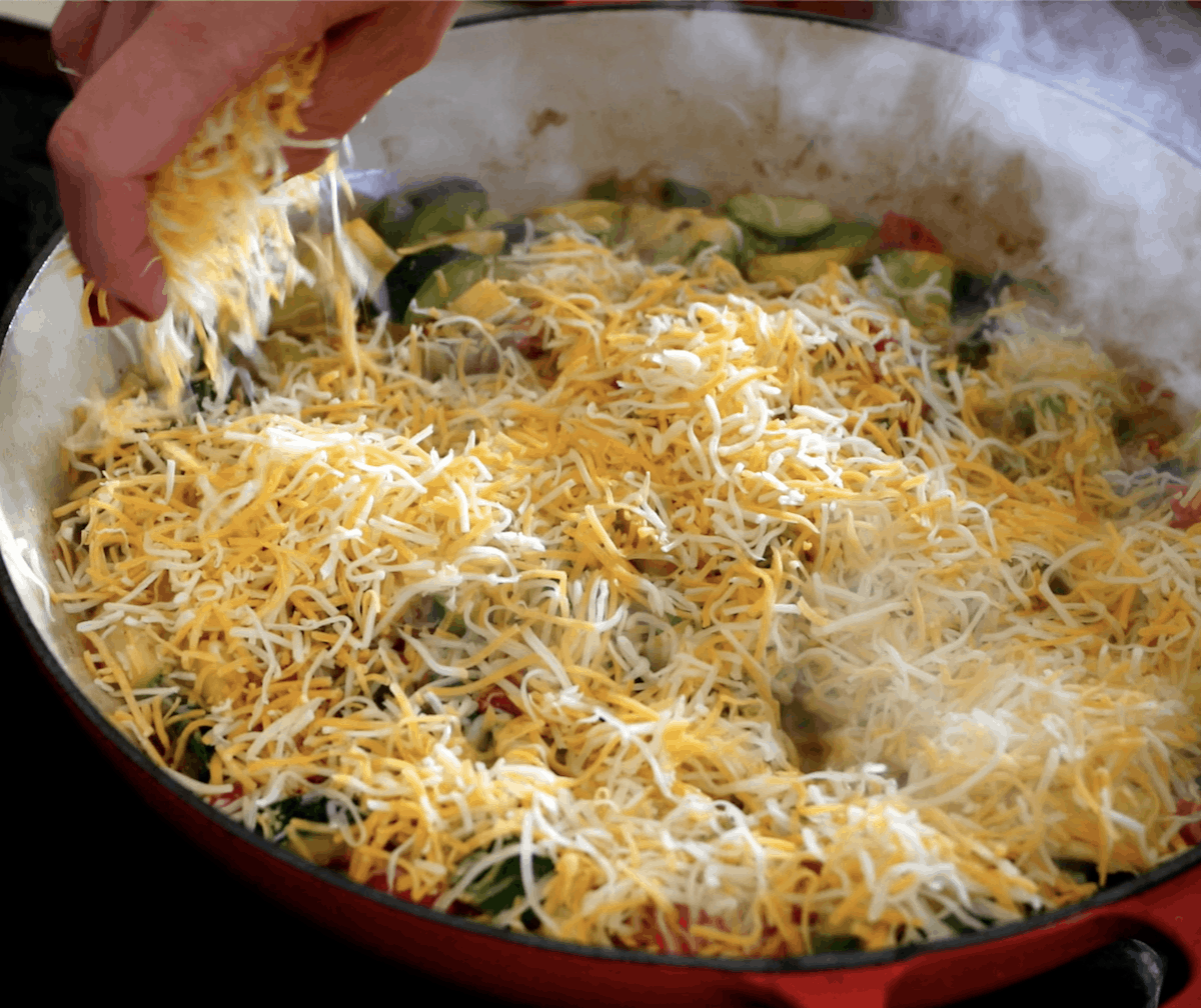 A pan of Calabacitas, a Mexican side dish made with sautéed zucchini and peppers getting cooked on the stoves and a hand putting cheese on top.