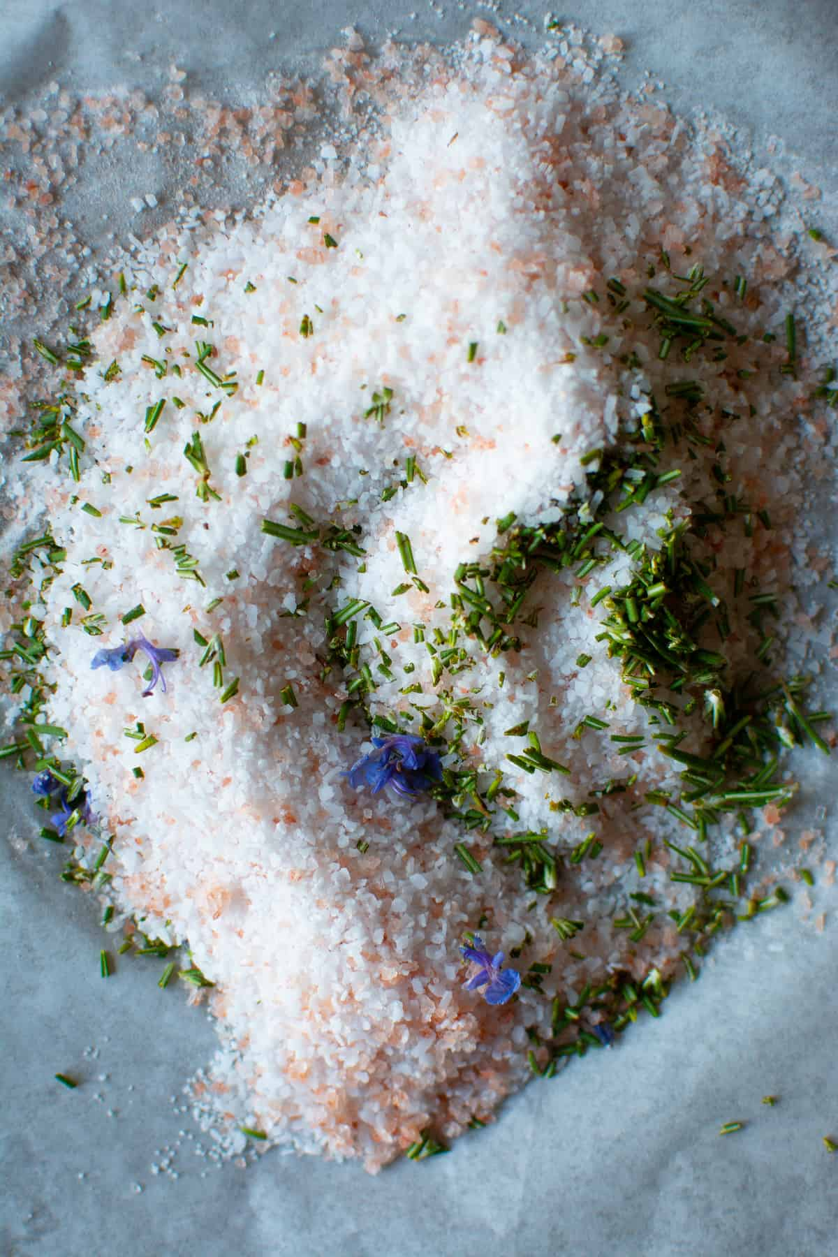 Pink and white salt with fresh chopped rosemary and purple rosemary flowers on a piece of parchment paper.