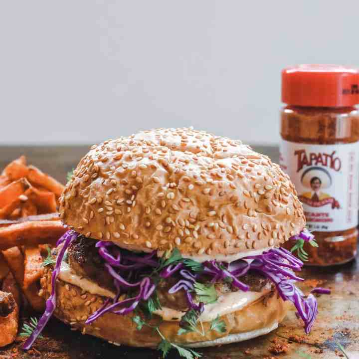 A turkey burger sitting on a wood table with a jar of Tapatio spice mix sitting behind it along with some sweet potato fries.