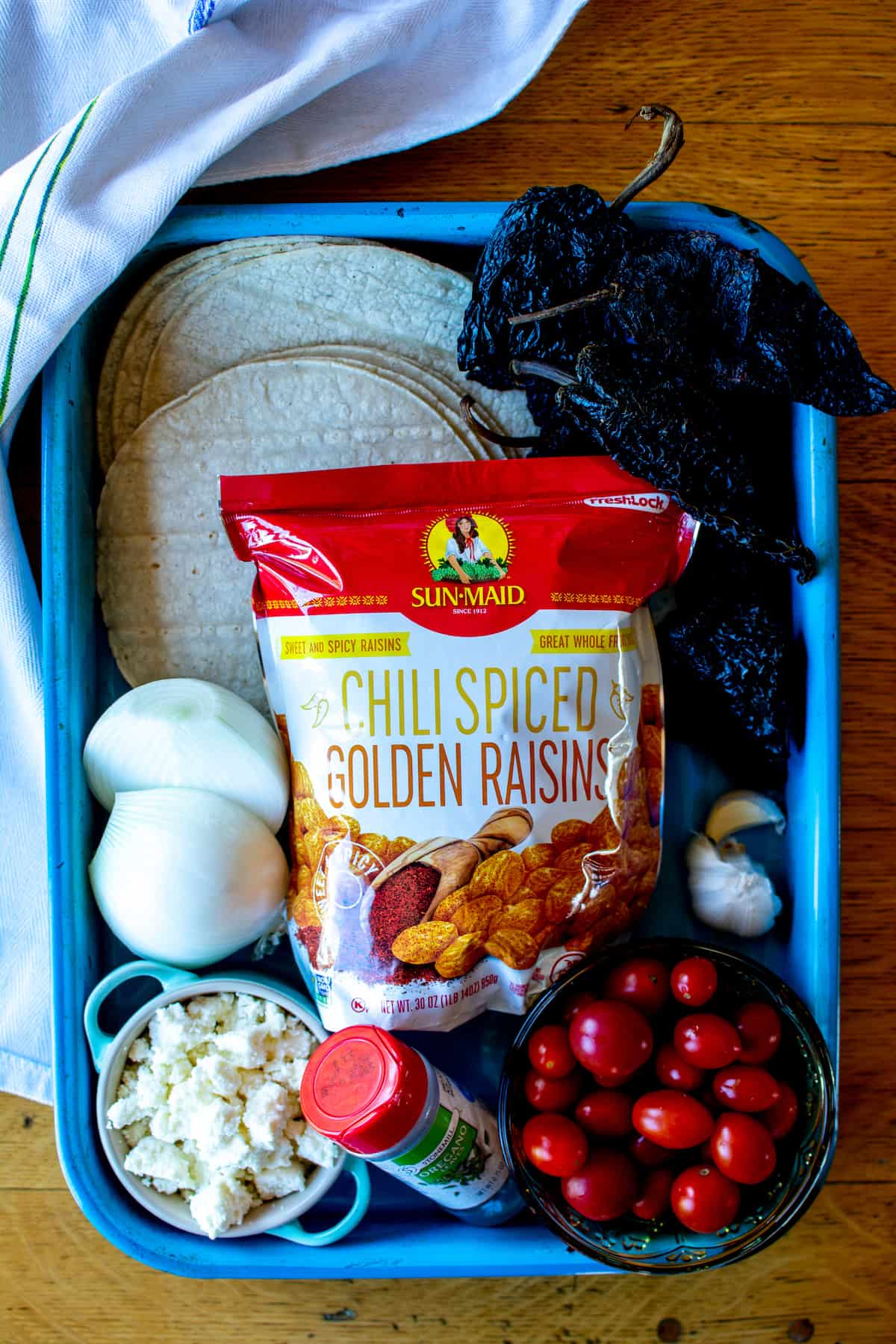 An overhead image of the ingredients to make cheese enchiladas, including golden raisins, dried chiles, corn tortillas, cherry tomatoes and onions.