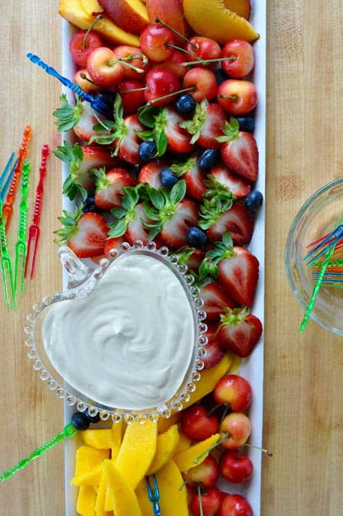 A tray of cut strawberries, blueberries, nectarines, mango slices, and cherries with a dish of creamy dip on one side.