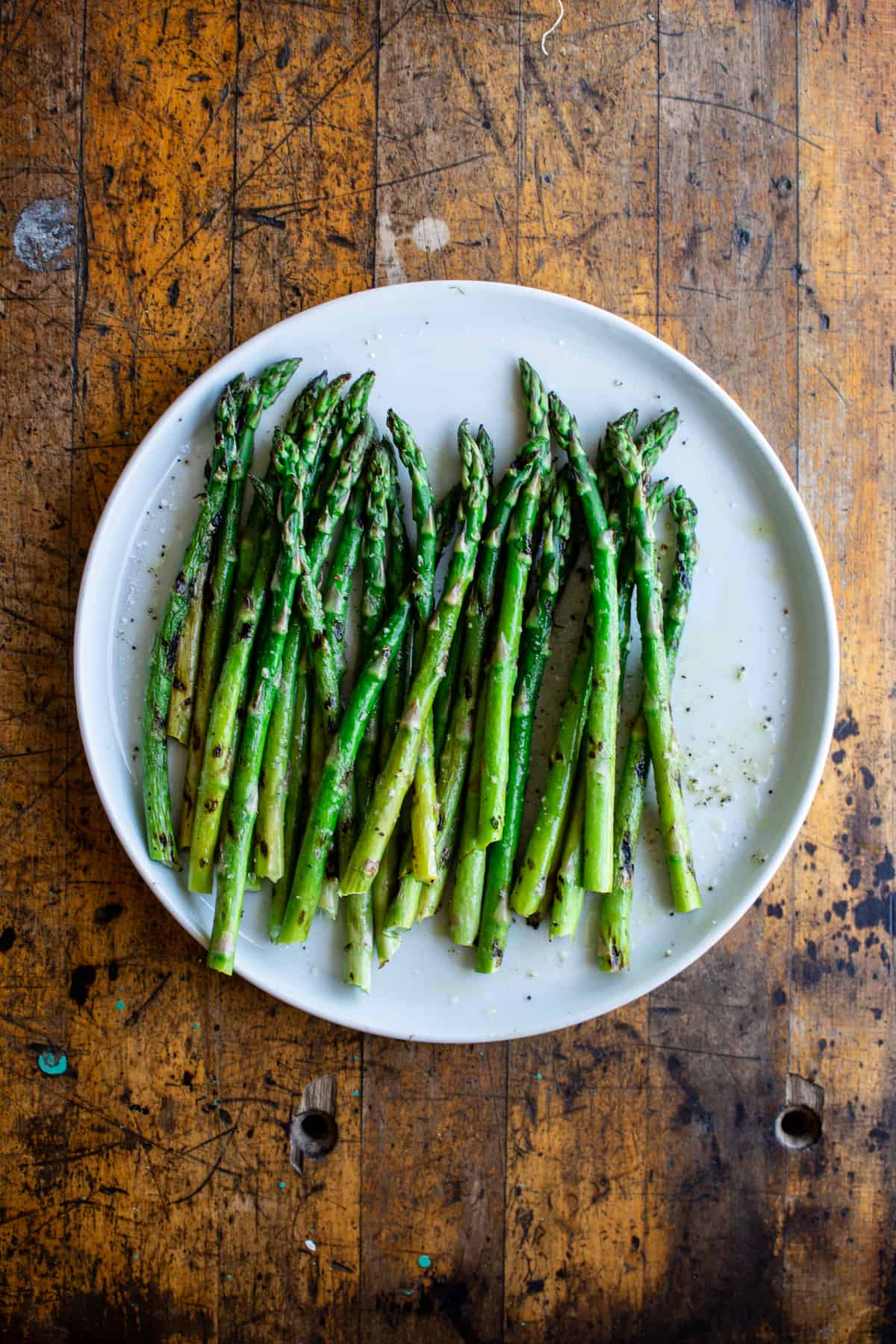 A white plate sitting on a wood table with grilled asparagus on it.