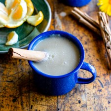 A blue mug filled with atole with a cinnamon stick sticking off to one side sitting on a wood table with a small plate of oranges behind it.
