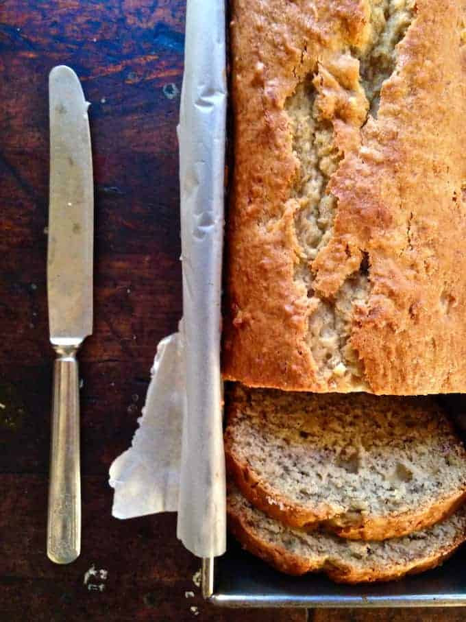 A pan of banana bread sitting on a wood table with two slices cut out of it and a butter knife sitting near by.