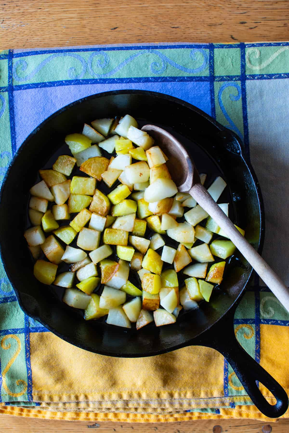 Crispy fried potatoes in a black cast iron skillet with a wooden spoon in the pan. The pan is sitting on a blue and green tablecloth.