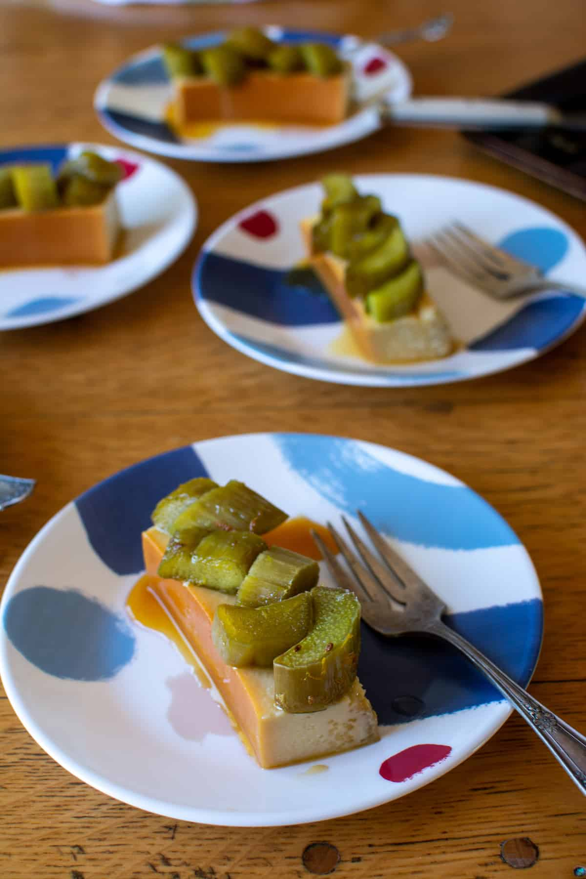 Pieces of flan with green pieces of rhubarb on top sitting on blue and white dessert plates with forks on the plates.