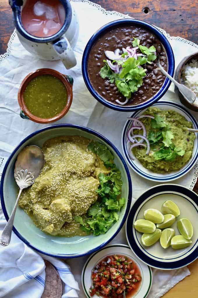 Several dishes of food including chicken mole verde, black beans, salsa verde, guacamole, and limes that are sitting on a white tablecloth.