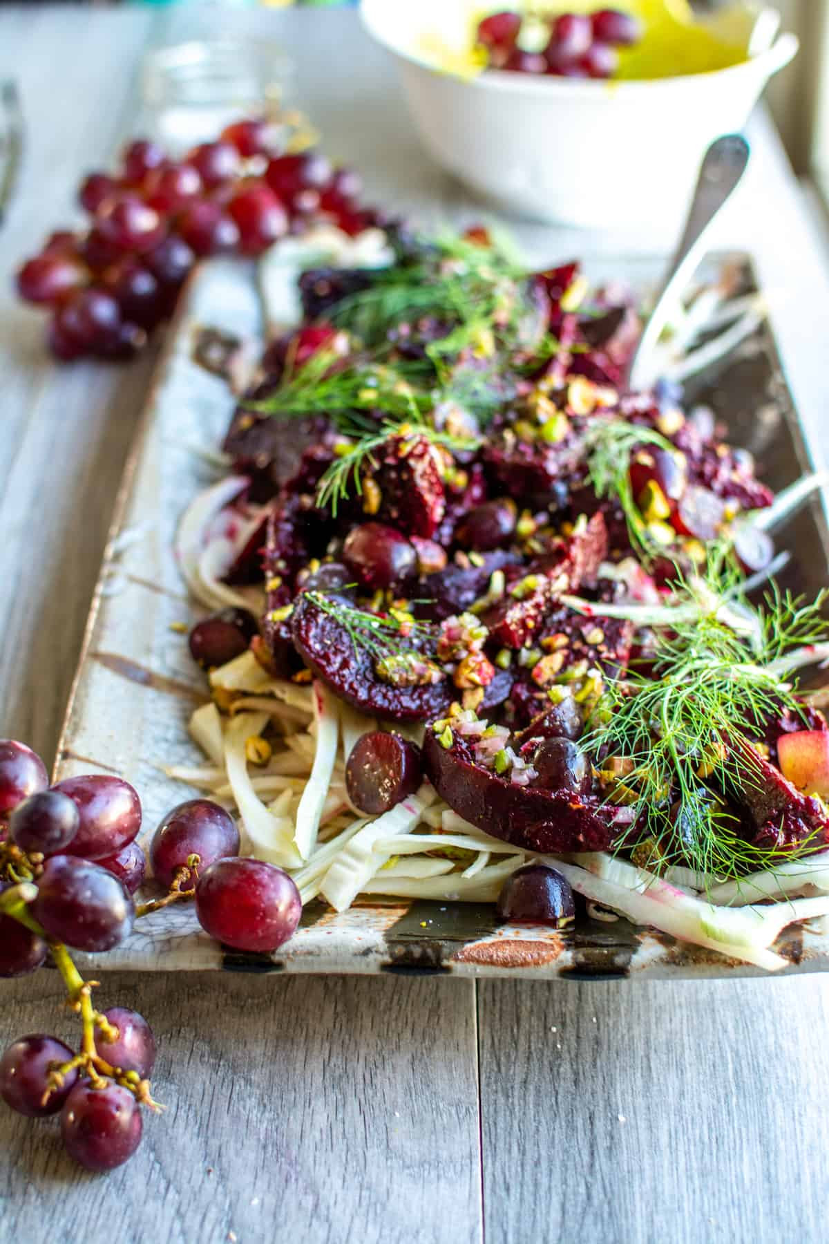 A rectangular ceramic platter filled with roasted beets, sliced fennel, red grapes, and chopped pistachios.