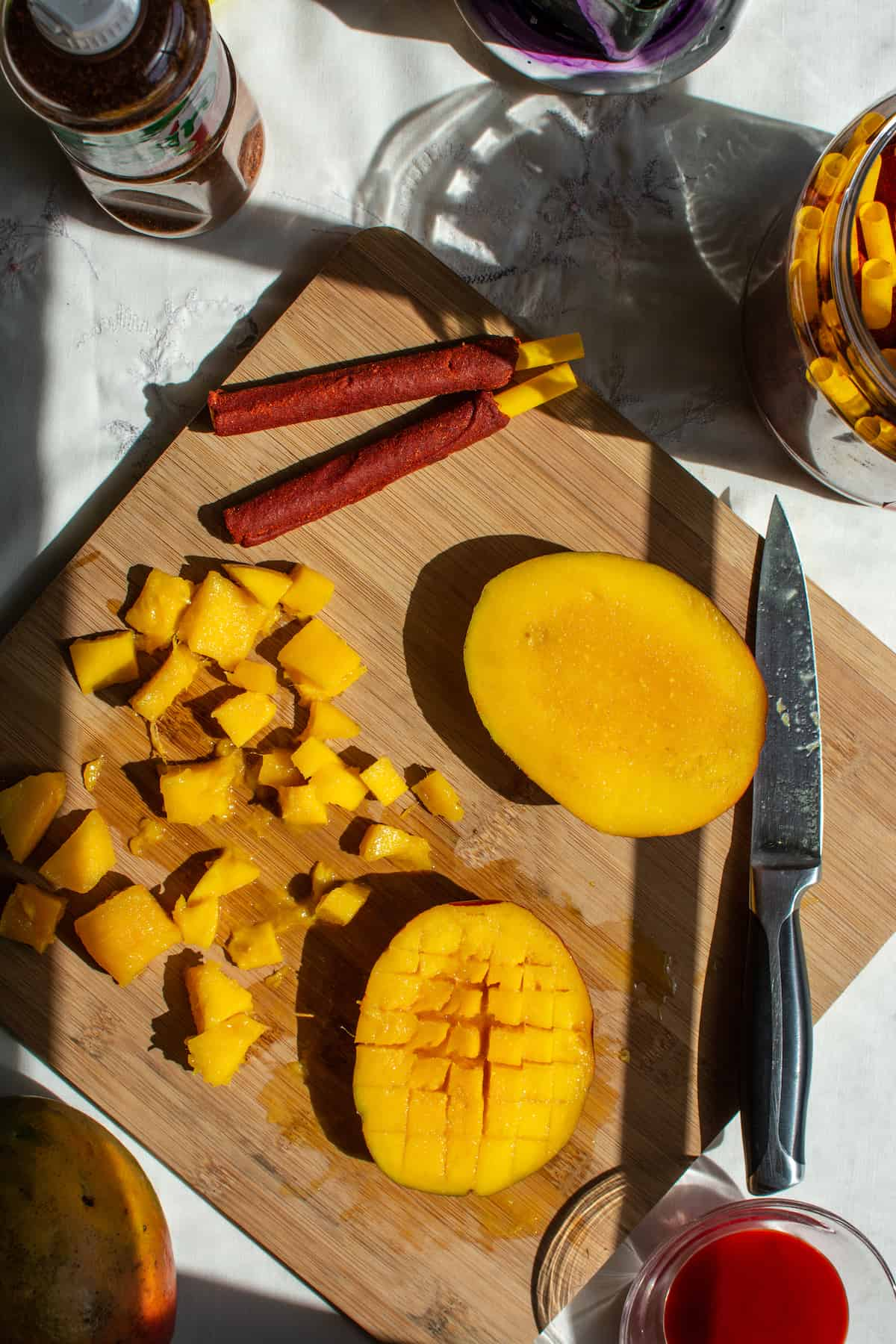 Overhead image of a mango being cut into small pieces sitting on a wood cutting board with a knife and two tamarind straws.