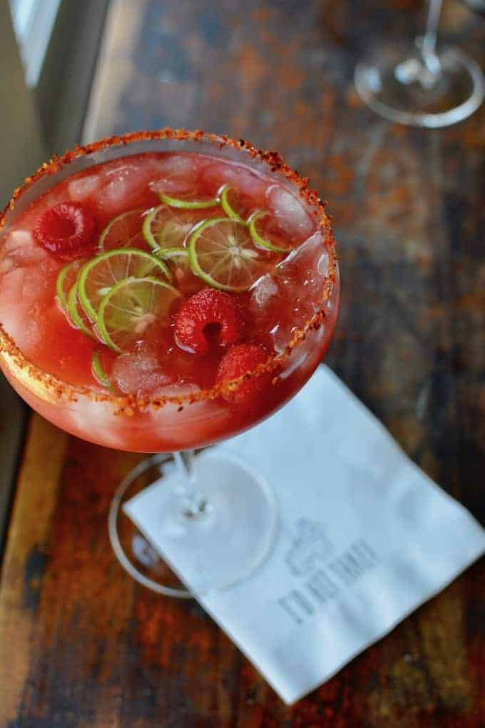 A margarita glass filled with a raspberry margarita with raspberries and key lime slices floating on top.
