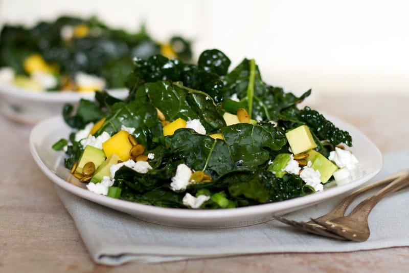Two plates of kale salad sitting on a white counter with cubes of mango, avocado and feta on top of them and a sprinkling of pumpkin seeds.