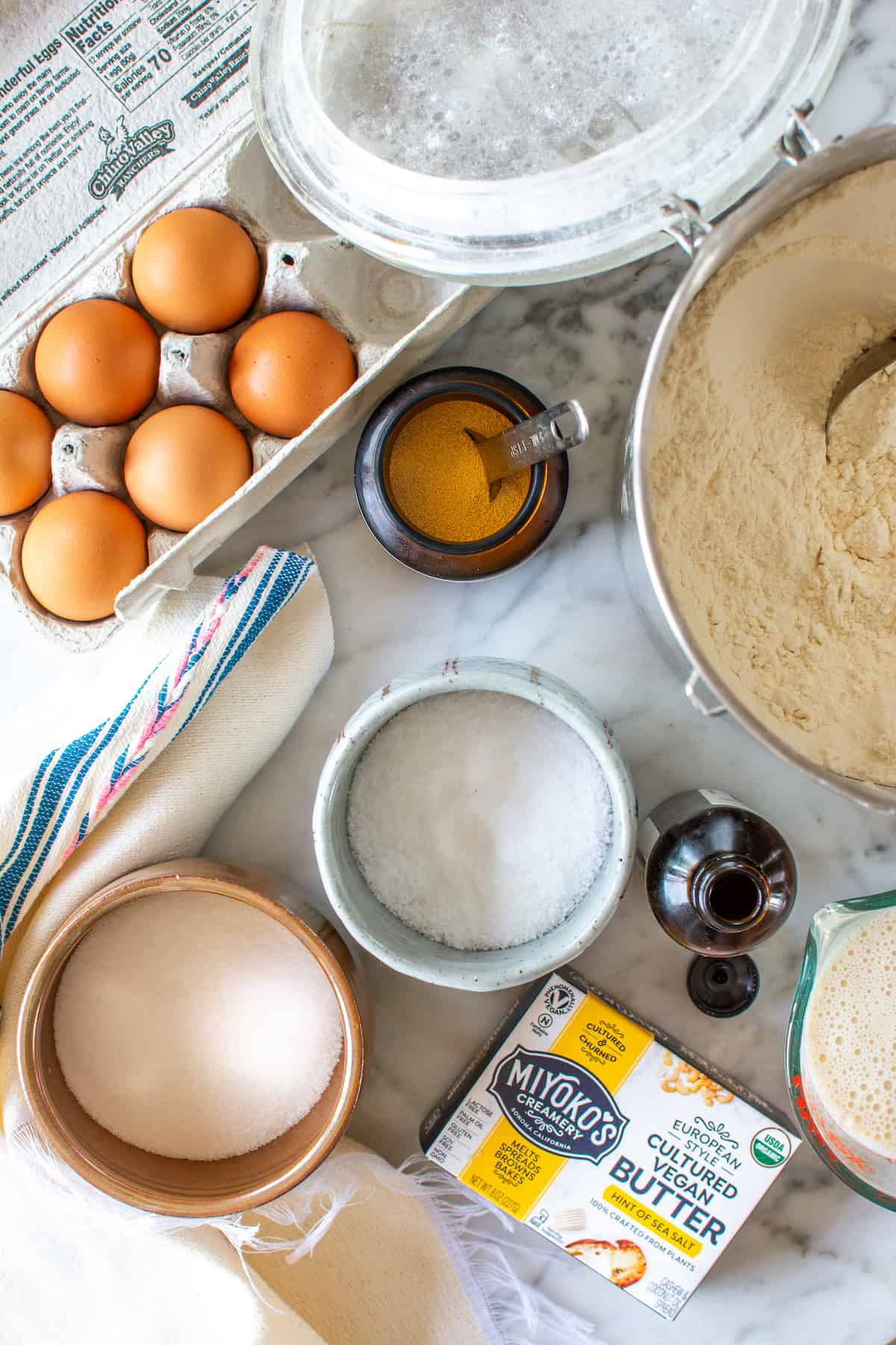 The ingredients to make concha rolls sitting on a marble table. Brown eggs in a carton, flour, yeast, salt, sugar, vanilla extract, and butter
